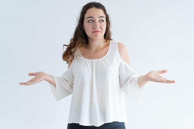 Retrato de mujer joven confundida encogiéndose de hombros