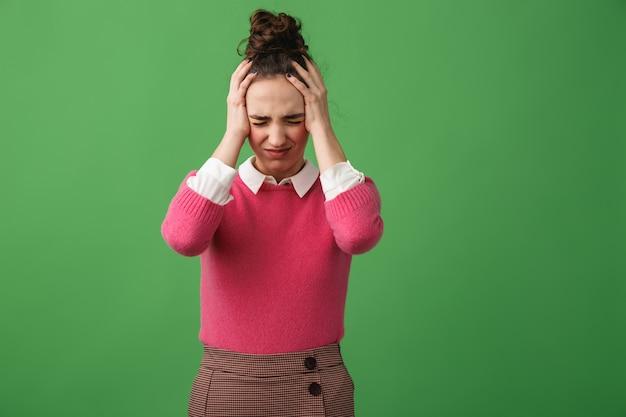 Retrato de una mujer joven confundida que se encuentran aisladas sobre verde