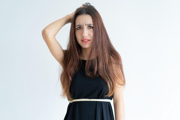 Retrato de mujer joven confundida rascándose la cabeza