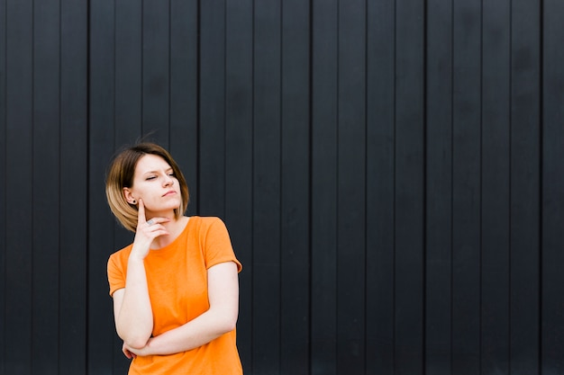 Retrato de una mujer joven contemplada de pie contra la pared negra