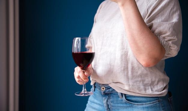 Retrato de una mujer joven con una copa de vino tinto en la mano contra la pared azul