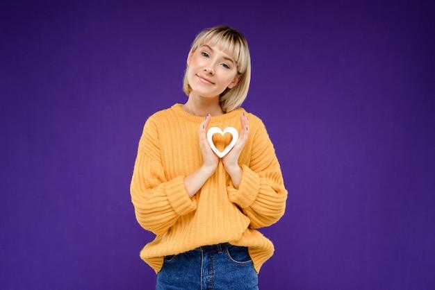 Retrato de mujer joven con corazón de decoración sobre pared púrpura