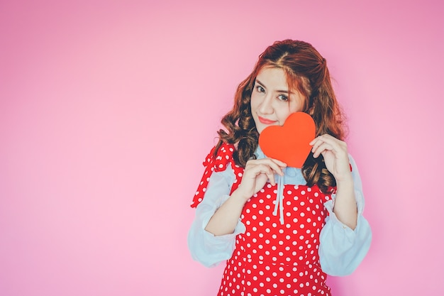 Retrato de mujer joven con corazón rojo delante de sus ojos sobre fondo rosa