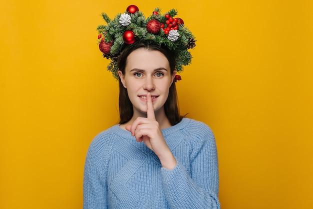 Retrato de mujer joven en corona de navidad