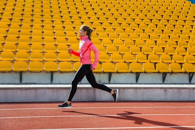 Retrato de una mujer joven corriendo en el estadio al aire libre