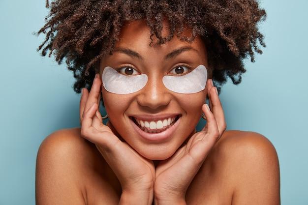 Retrato de mujer joven con corte de pelo afro y parches en los ojos