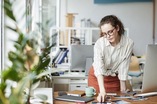 Retrato de mujer joven creativa revisando fotografías mientras trabaja en la edición y publicación en la oficina moderna, espacio de copia