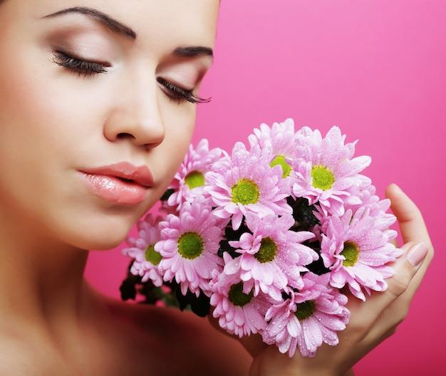 Retrato de mujer joven con crisantemo rosa