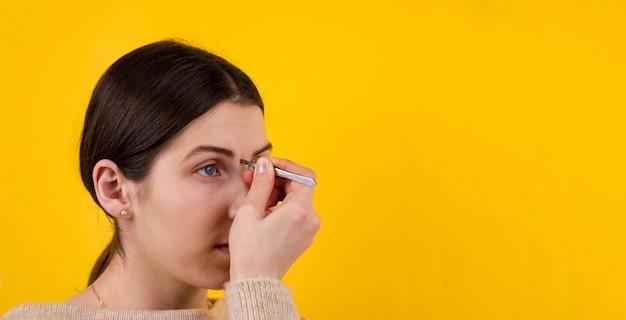 Retrato de mujer joven depilarse las cejas con pinzas sobre fondo amarillo.