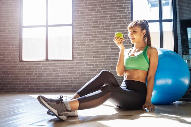 Retrato de mujer joven deporte con manzana verde en el gimnasio
