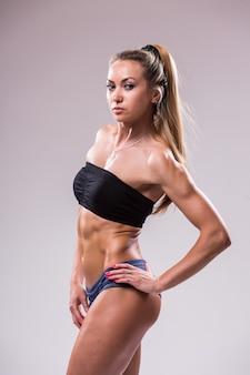 Retrato de mujer joven deportiva con cuerpo musculoso, posando sobre un fondo gris