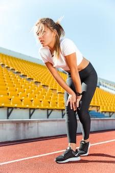 Retrato de una mujer joven descansando después de correr en el estadio