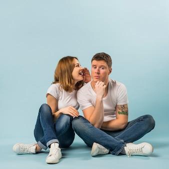 Retrato de mujer joven diciendo un secreto a su novio contra el fondo azul