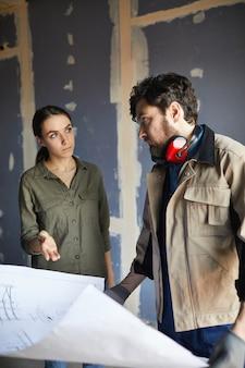 Retrato de mujer joven discutiendo planos de planta con contratista de construcción mientras está de pie contra la pared seca en casa en construcción, espacio de copia