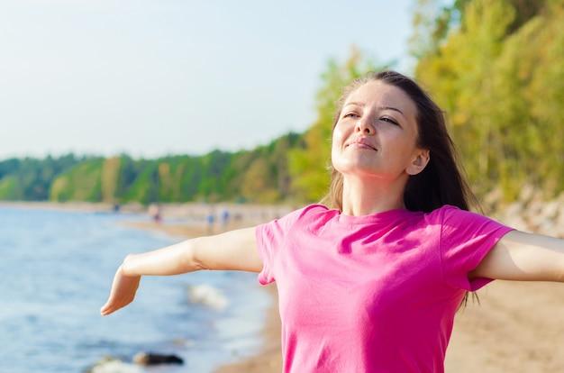Retrato de una mujer joven disfrutando del aire fresco en la playa