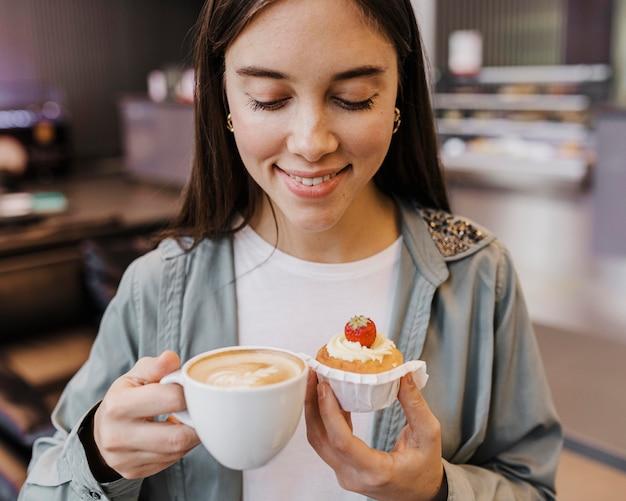 Retrato de una mujer joven disfrutando de café y pastel