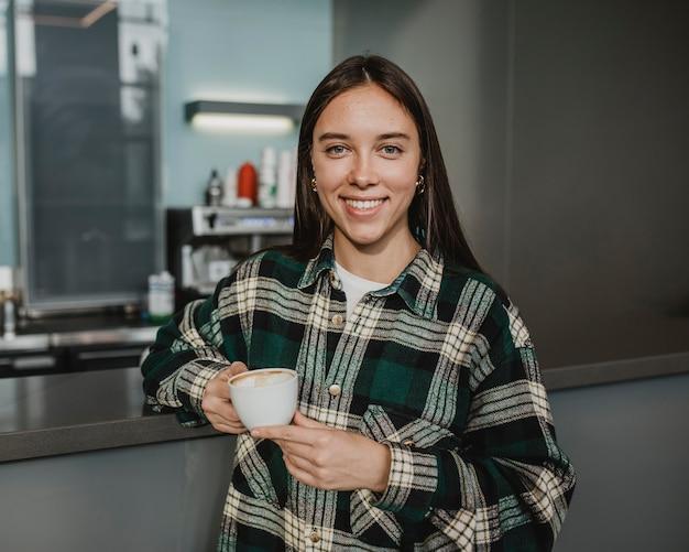 Retrato de una mujer joven disfrutando de un café