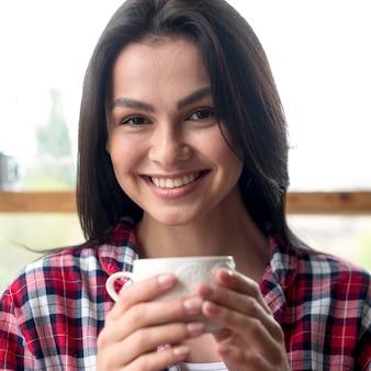 Retrato de mujer joven disfrutando de una taza de té