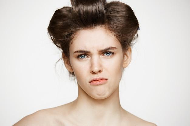 Retrato de mujer joven disgustado en rizadores para el cabello. cosmetología de belleza y spa.