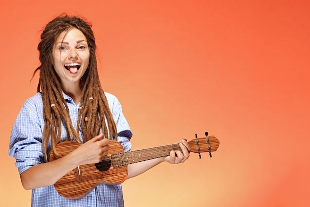 Retrato de mujer joven divertida jugando ukelele felicidad y concepto despreocupado