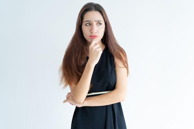 Retrato de mujer joven dudosa de pie con la mano en la barbilla