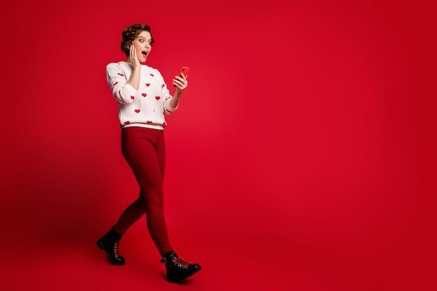 Retrato de una mujer joven con elegante puente de moda aislado en la pared roja