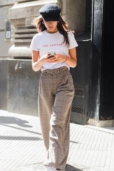 Retrato de una mujer joven elegante que camina en la calle que manda un sms en el teléfono elegante
