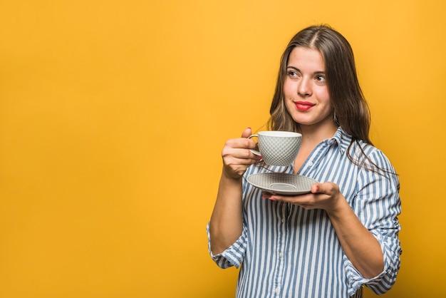Retrato de una mujer joven elegante que sostiene la taza en las manos que miran lejos