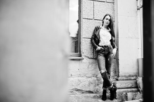 Retrato de mujer joven elegante vistiendo chaqueta de cuero y jeans rotos en las calles de la ciudad