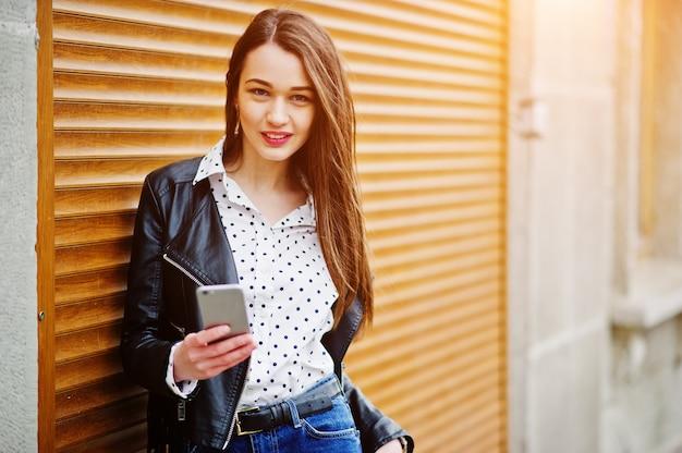 Retrato de mujer joven elegante vistiendo chaqueta de cuero con teléfono móvil a mano