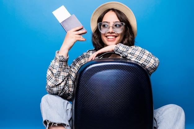 Retrato de una mujer joven emocionada vestida con ropa de verano con pasaporte con billetes de avión mientras está de pie con una maleta aislada