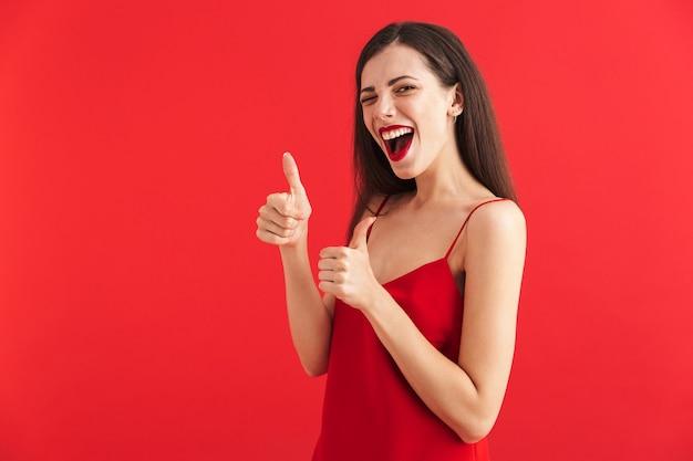 Retrato de una mujer joven emocionada en vestido aislado, mostrando los pulgares para arriba
