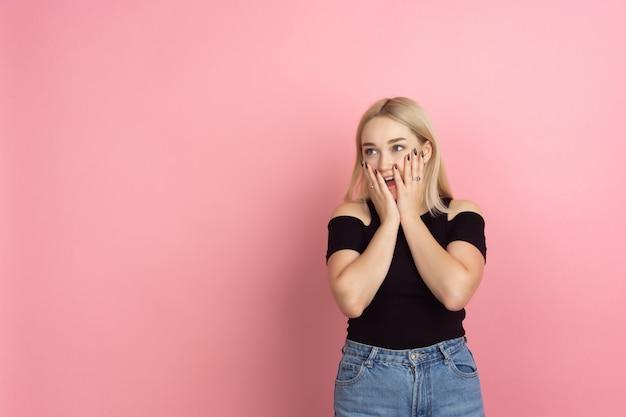 Retrato de mujer joven con emociones brillantes en la pared del estudio de coral rosa