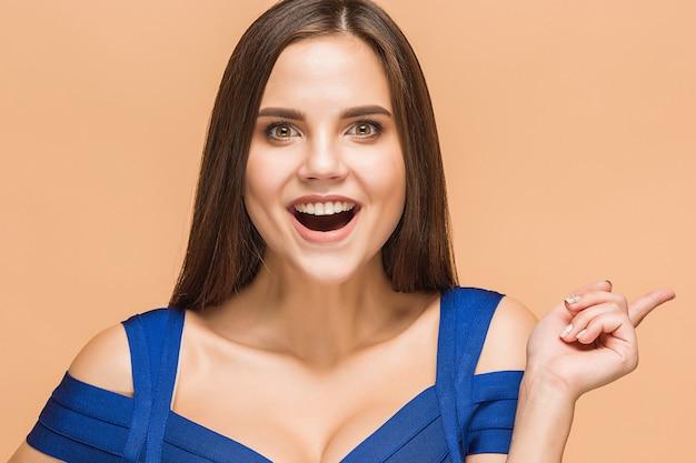 Retrato de mujer joven con emociones felices sobre fondo marrón