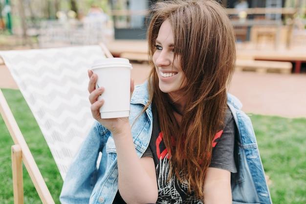 Retrato de mujer joven encantadora con cabello largo oscuro vestida con chaqueta vaquera está sentada en el parque con una taza de café y mirando a un lado con gran sonrisa. buen dia soleado. estado de ánimo relajado. Foto gratis