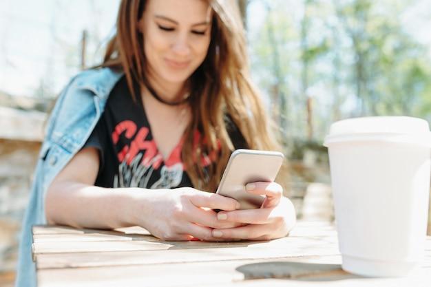 Retrato de mujer joven encantadora de cerca está sentada en el parque con una taza de café y mirando su teléfono. concéntrese en la taza. buen dia soleado. estado de ánimo relajado.