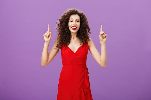 Retrato de mujer joven encantadora entusiasta de ensueño con el pelo rizado en elegante vestido rojo levantando los brazos hacia arriba y sonriendo con diversión y felicidad posando sobre la pared púrpura.