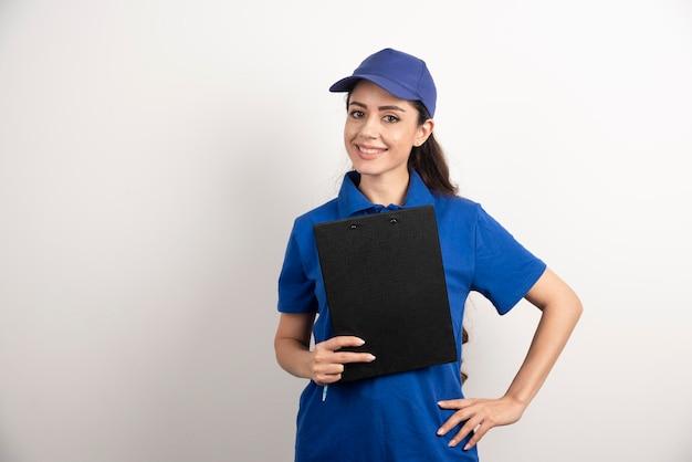 Un retrato de una mujer joven de entrega con portapapeles. foto de alta calidad Foto gratis