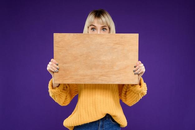 Retrato de mujer joven con escritorio de madera sobre pared púrpura