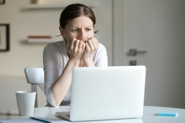 Retrato de una mujer joven en el escritorio con el ordenador portátil, el miedo