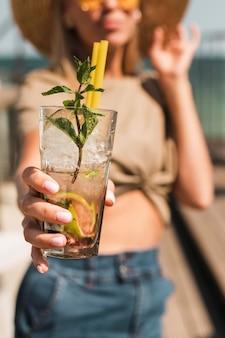 Retrato de mujer joven con estilo disfrutando de un cóctel de verano