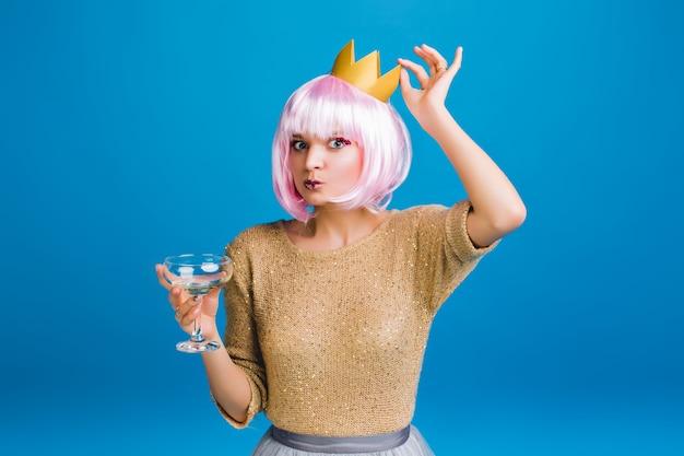 Retrato mujer joven con estilo divertido en suéter dorado, corte de pelo rosa, corona en la cabeza. divirtiéndose, bebiendo champán, celebrando la fiesta de año nuevo, cumpleaños.