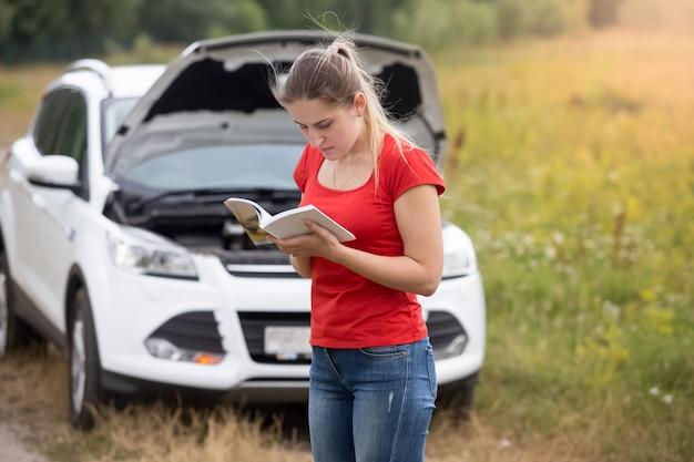 Retrato de mujer joven estresada de pie en el coche roto y leyendo el manual del propietario