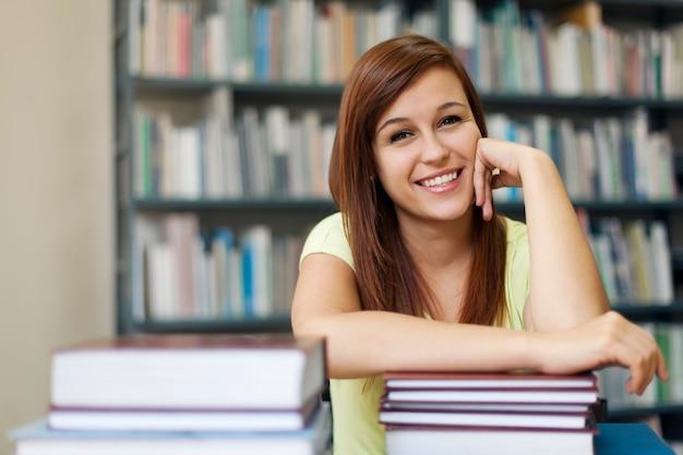 Retrato de mujer joven estudiante en biblioteca