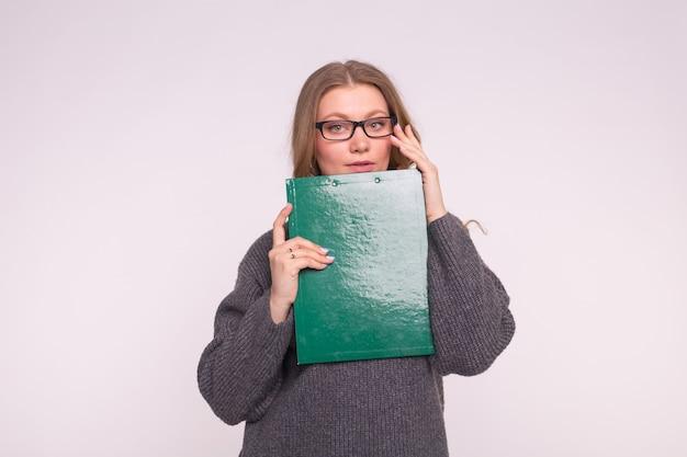 Retrato de mujer joven estudiante con clip en manos sobre fondo blanco.