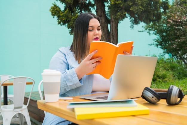Retrato, de, mujer joven, estudiar, con, computadora portátil, y, libros, mientras, sentado, aire libre, en, cafetería