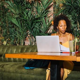 Retrato de mujer joven examinando el documento con laptop y cóctel en mesa de madera