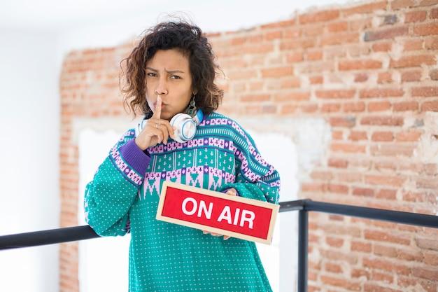 Retrato de una mujer joven y exótica pidiendo silencio. tiene en la mano un cartel con el texto on air. espacio para texto.