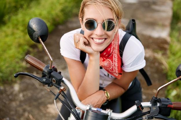 Retrato de mujer joven extrema feliz con sonrisa brillante, vestida con ropa de motociclista de moda, descansa sobre una moto rápida, le gusta su afición. personas, estilo de vida activo y concepto de deporte extremo.