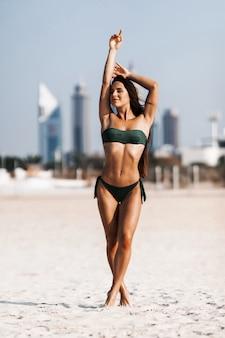 Retrato de mujer joven feliz en bikini blanco de pie en agua de mar